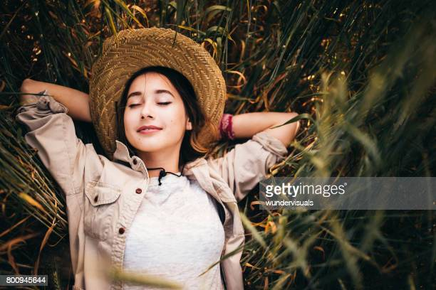 Woman farm worker laying in field resting and daydreaming
