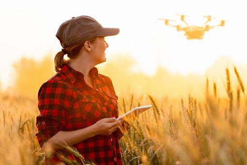 Woman farmer controls drone 1140405651