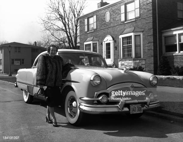 Woman fashionably dressed in a waist lenght fur coat and heels, smiles and stands next to a 1953 Packard automobile, Chicago, 1953.