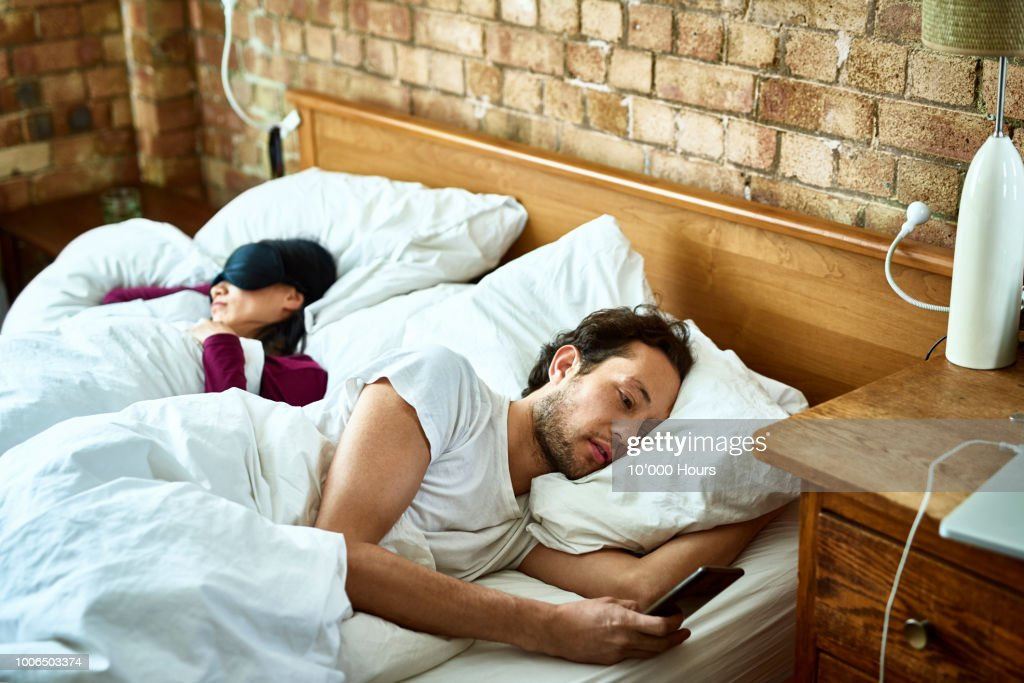 Woman fast asleep next to partner who is checking his smartphone : Stock Photo