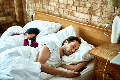 Woman fast asleep next to partner who is checking his smartphone - gettyimageskorea