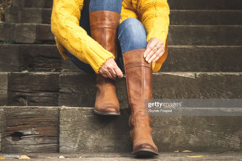 Woman fasten zipper on her leather boot : Stock Photo