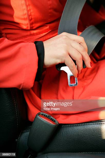 A woman fastening a seat belt of a car