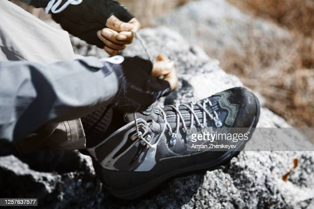 woman fastening laces of hiking boots - lace fastener stock pictures, royalty-free photos & images