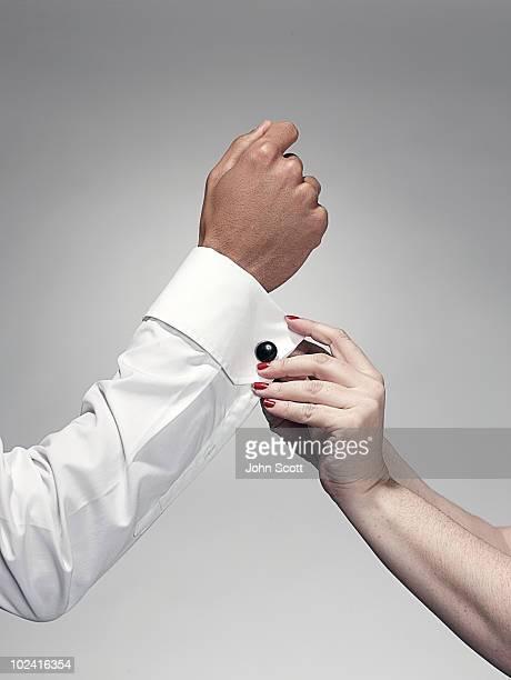 Woman fastening man's cuff link