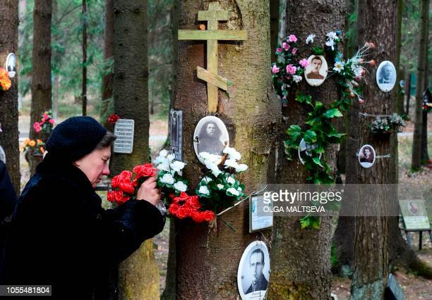 TOPSHOT A woman fastens flowers to the tree with portraits of victims of Soviet dictator Joseph Stalin's purges at the memorial where the victims...