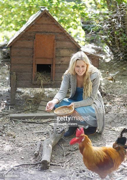 Woman feedin chickens in countryside.