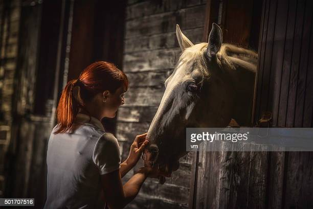 Woman feeding a horse in a stable at night