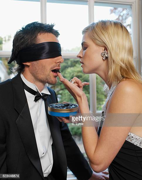 Woman Feeding Caviar to Blindfolded Man