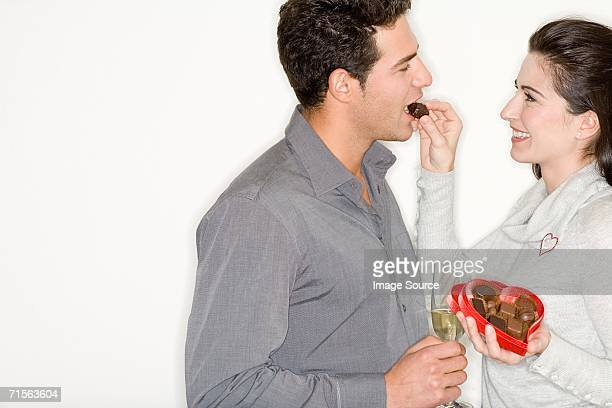 Woman feeding chocolates to boyfriend