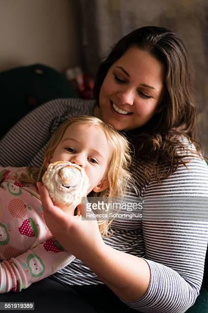 woman feeding cinnamon bun to young girl - sweet bun stock pictures, royalty-free photos & images
