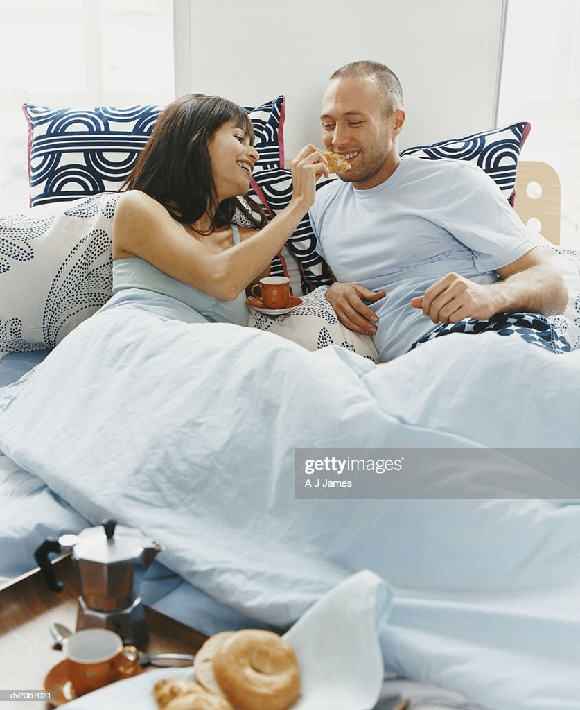 Woman Feeding Food to a Man in Bed : Stock Photo