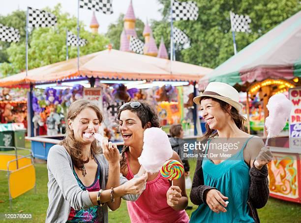 Woman feeding friend candyfloss at funfair.