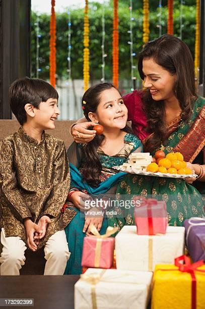 Woman feeding gulab jamun to her daughter on Diwali