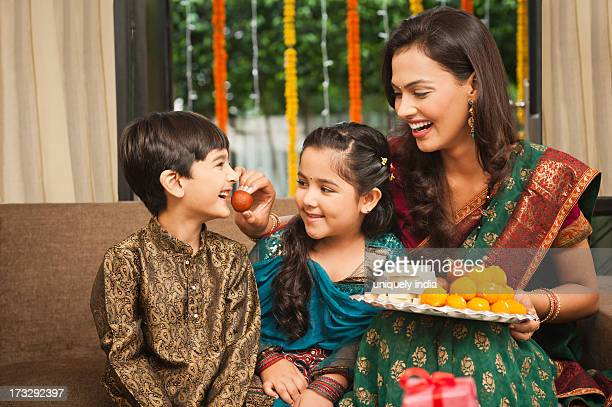 woman feeding gulab jamun to her son on diwali - diwali sweets stock photos and pictures