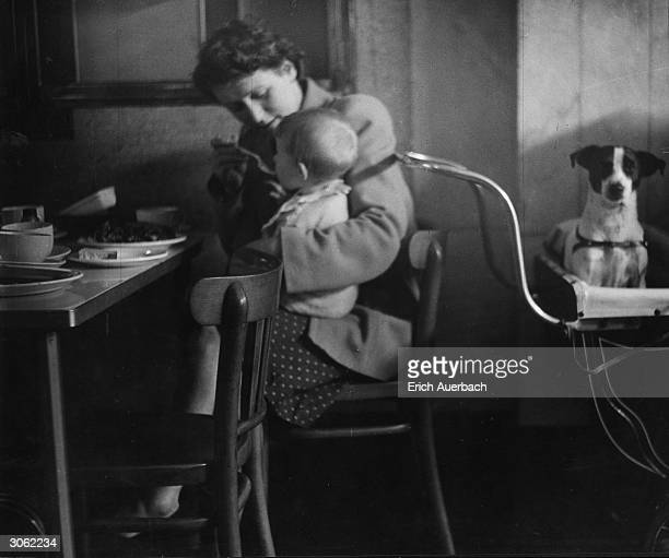 A woman feeding her baby in a Lyon's teashop on the corner of the Edgware Road and Harrow Road London while her dog sits in the pram