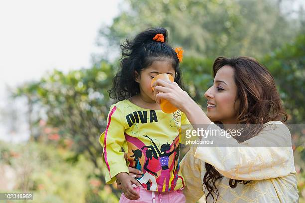Woman feeding juice to her daughter in a park