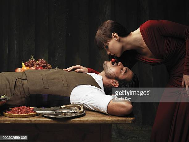 Woman feeding man cherry from her mouth, side view