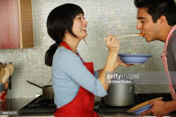 Woman feeding man in kitchen