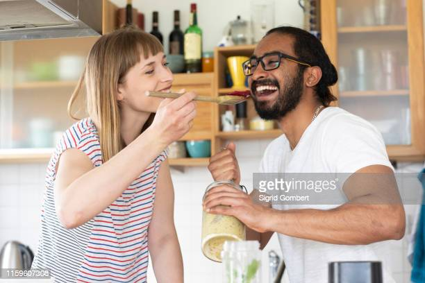 woman feeding man with wooden spoon in kitchen - sigrid gombert fotografías e imágenes de stock