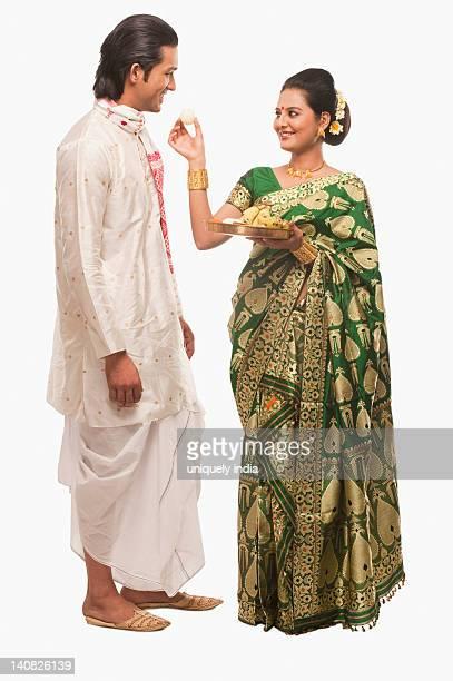 woman feeding prasad to a man on bihu festival - kurta stock pictures, royalty-free photos & images