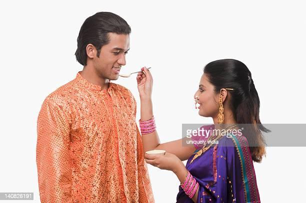 Woman feeding prasad to a man on Gudi Padwa festival