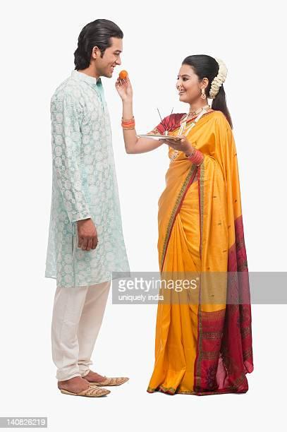 woman feeding prasad to a man on gudi padwa festival - gudi padwa stock pictures, royalty-free photos & images