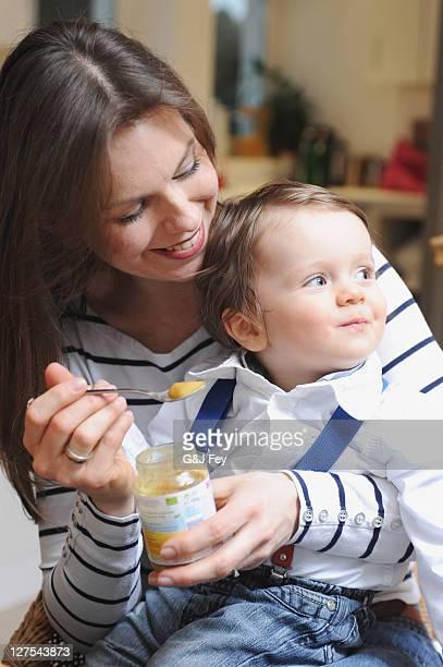 Woman feeding toddler son baby food