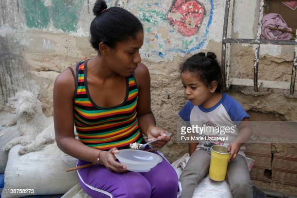 A woman feeds a girl at La Bombilla slum on April 18 2019 in Caracas Venezuela Political and economic crisis has triggered a food emergency in...