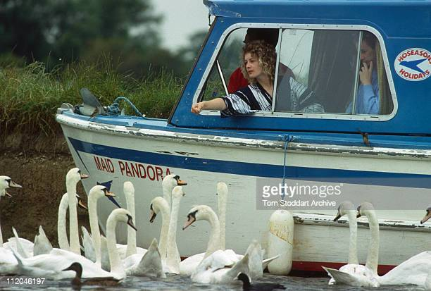 Woman feeds bread to swans from her motor boat moored on the River Thames at Windsor. The swans have been claimed by the Crown since the 12th century...