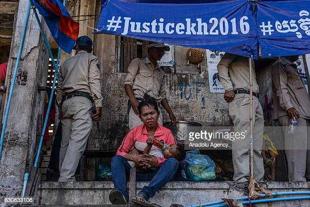 A woman feeds her baby as police arrive during a protest at the Borei Keila site in Phnom Penh Cambodia on January 3 2017Families were evicted from...