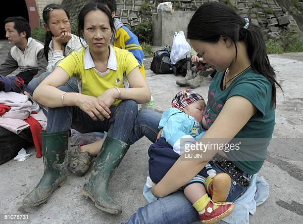A woman feeds her baby as they take a rest from their exodus in Wenchuan County along a collapsed mountain road the only escape route from the...