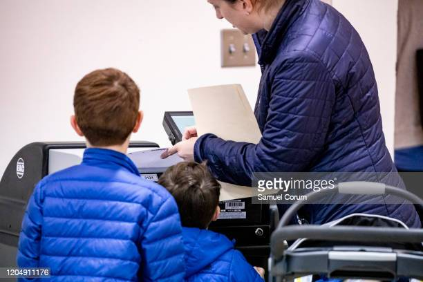 A woman feeds her ballot into a voting machine as her sons watch during the Democratic presidential primary elections at the McKinley Elementary...