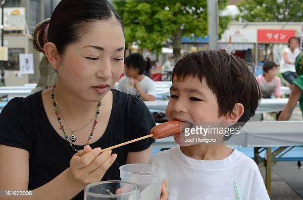 Woman feeds hot dog to a little boy