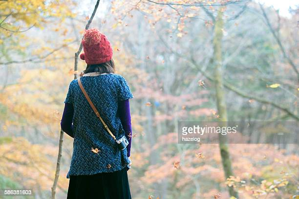 Woman feel the Autumn breeze with falling leaves