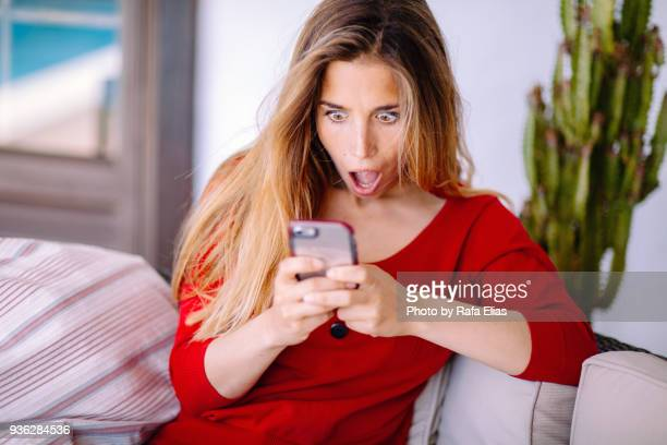 woman feeling big surprise checking phone - shock stock pictures, royalty-free photos & images