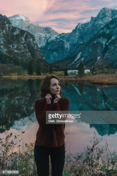 Woman feeling cold near the  lake in Alps at sunset