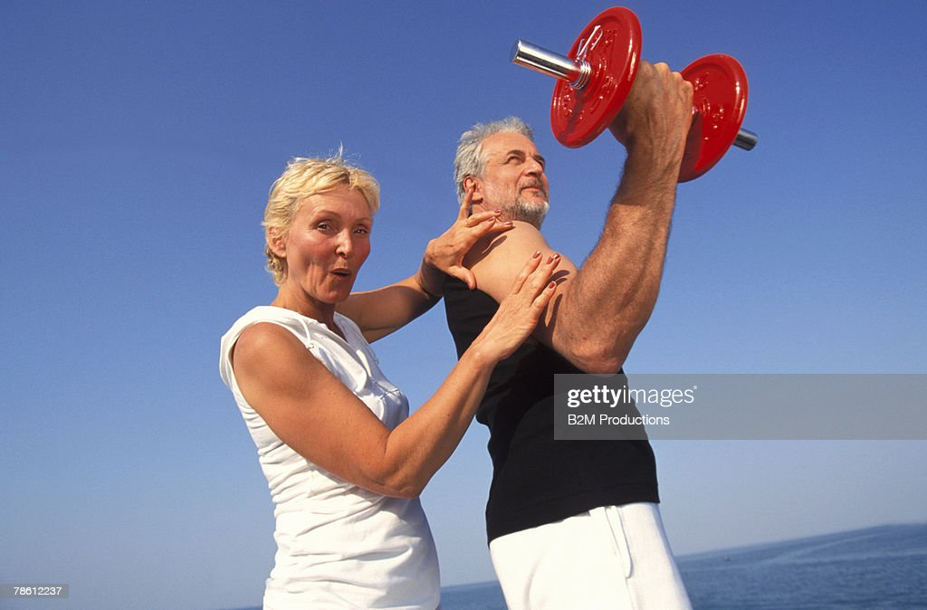 Woman feeling man's bicep : Stock Photo