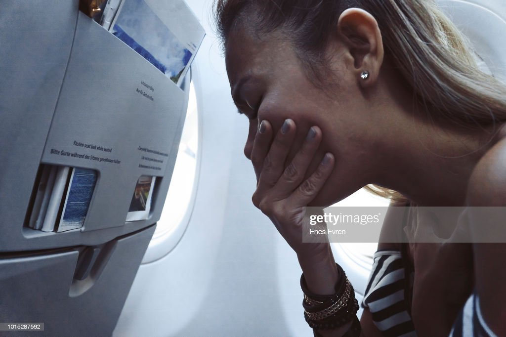 Woman feeling sick and puking in Airplane : Stock Photo