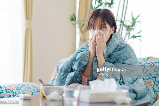 ティッシュペーパーで鼻を吹いて家で気分が悪い女性 - ナイトウェア ストックフォトと画像