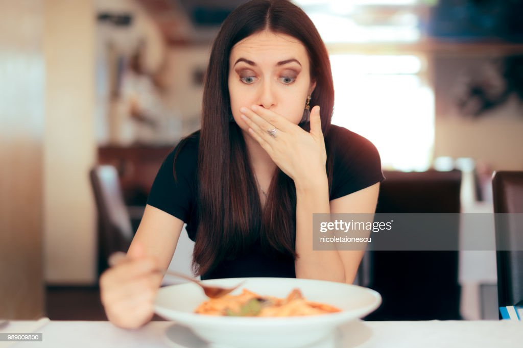 Woman Feeling Sick While Eating Bad Food in a Restaurant : Stock Photo