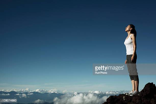 woman feeling the wind at the mountain