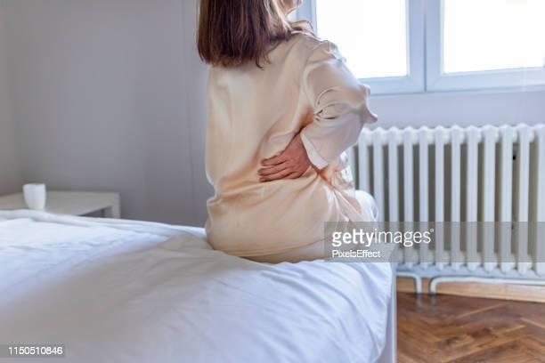 frau spürt rückenschmerzen massieren muskeln - menschlicher rücken stock-fotos und bilder