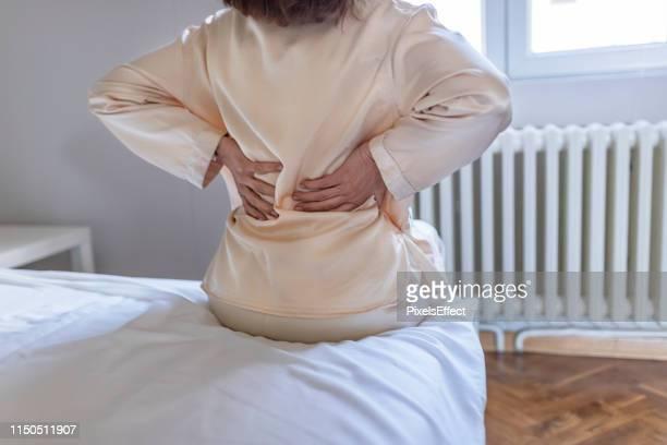 女性は背中に痛みを感じるマッサージ痛む筋肉 - 下背部痛 ストックフォトと画像