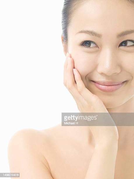 woman feels the softness of her skin - 後ろで束ねた髪 ストックフォトと画像