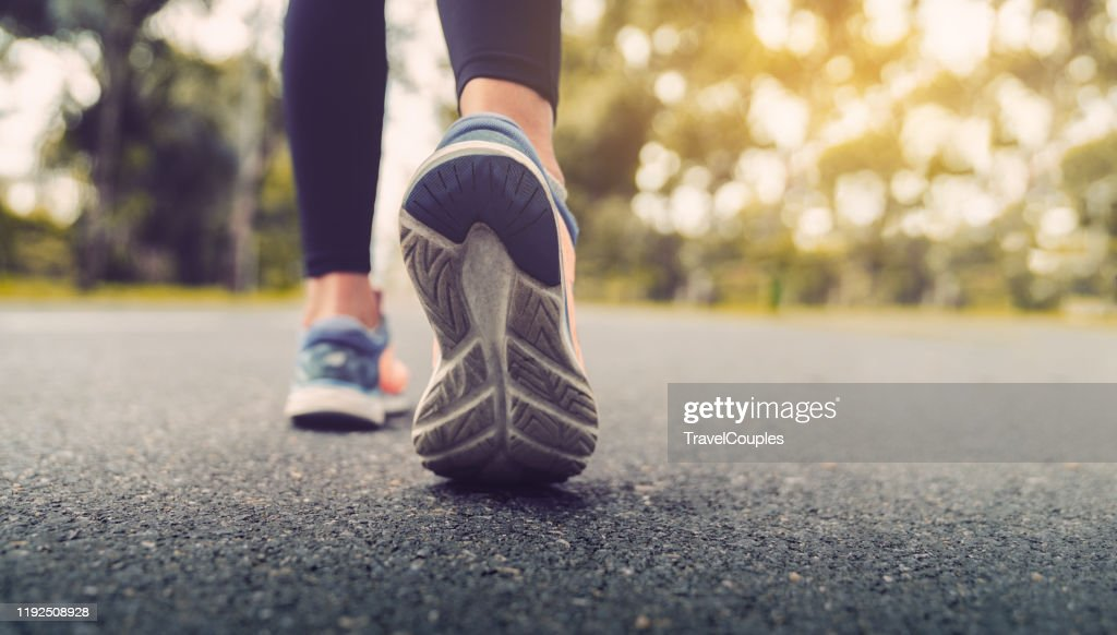 Woman feet running on road closeup on shoe. Young fitness women runner legs ready for run on the road. Sports healthy lifestyle concept. : Stockfoto
