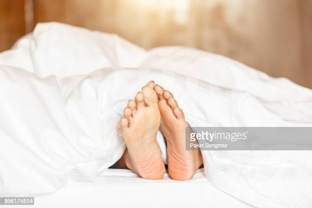 Woman feet under white blanket side view. Beautiful young woman feet with blue pedicure on the bed.