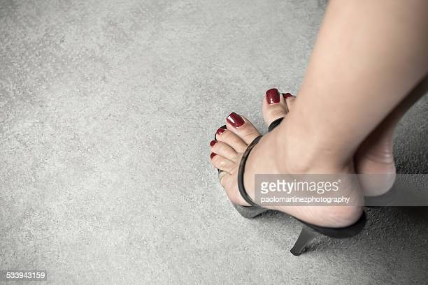 woman feet with red nail polish on high heels shoe - pretty toes and feet stock photos and pictures