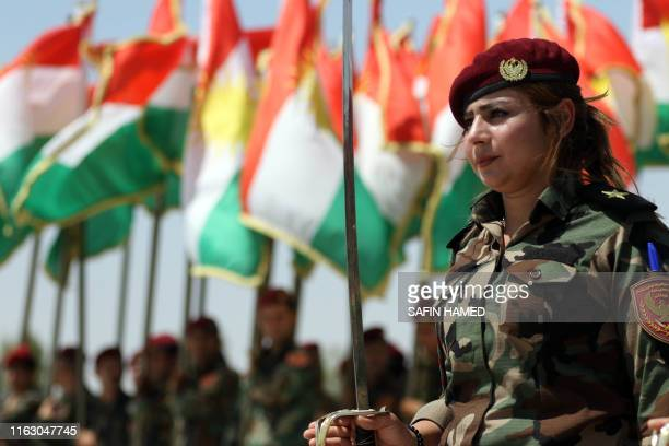 A woman fighter of the Iraqi Kurdish Peshmerga attends a ceremonial lineup past flying flags of Iraq's autonomous Kurdistan region during a training...