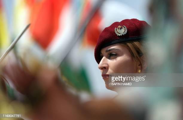 Woman fighter of the Iraqi Kurdish Peshmerga attends a ceremonial line-up past flying flags of Iraq's autonomous Kurdistan region, during a training...